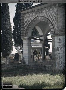 Turquie d'Asie, Brousse, Le porche de la Mouradié, le pavillon du bassin d'ablutions, au-delà des Cyprés. Une entrée du complexe de la Muradiye Camii (mosquée du sultan Murat II) , à l'arrière plan, une fontaine aux ablutions