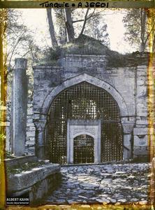 Turquie, Constantinople - Eyoub, Cimetière d'Eyoub - Vieux Turbé. Porte d'un mausolée : porte grillagée sur une allée pavée permettant d'accéder à une cour derrière l'Együp Sultan Camii (?)