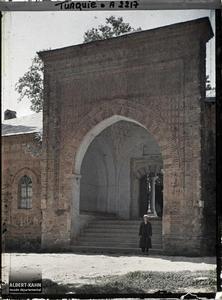 Turquie d'Asie, Brousse, Porte de la Médressé avec un hodja. Une entrée du complexe de la Muradiye Camii (mosquée du sultan Murat II) datant de 1424-1427