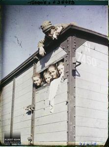 Thrace, Andrinople, La gare, Émigrants dans un wagon de marchandises. Quatre Grecs quittant la ville (une femme et trois enfants) passant la tête dans une ouverture de train de marchandises. Un soldat (grec ou allié ?) sur le toit