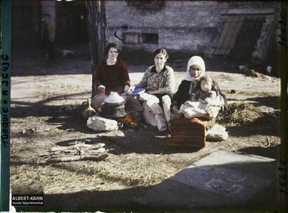Thrace, Andrinople, La gare, Cuisine improvisée. Trois femmes grecques dont l'une tenant un enfant, s'apprêtant à quitter la ville, assises aux abords de la gare, près d'un foyer improvisé